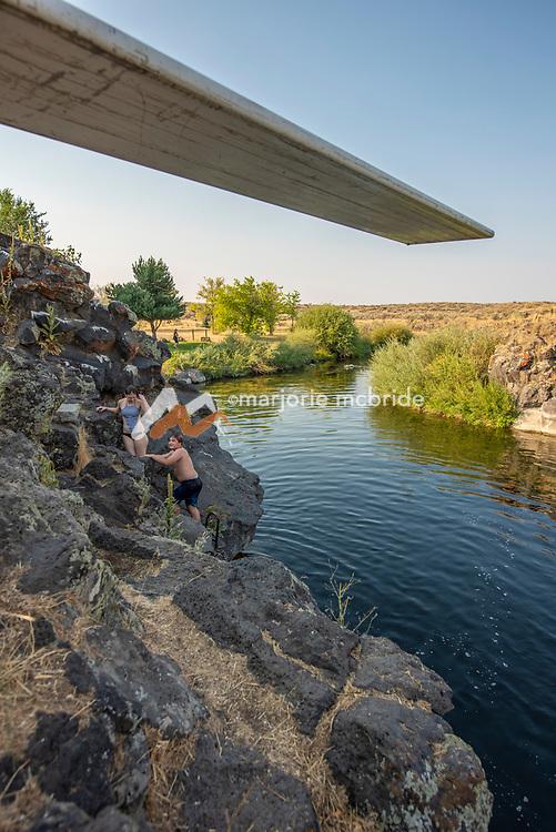 Three kids having fun jumping from the Ledges swimming hole in Richfield, Idaho.