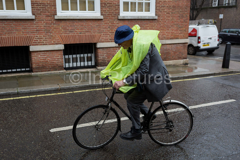 An elderly gentleman wearing a makeshift plastic cape cycles through the rain in a side street in Westminster SW1, on 14th March 2019, in London, England.
