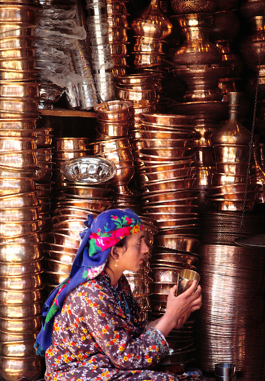 A young brass vendor shows a cup to a client in Srinagar, Kashmir, India.