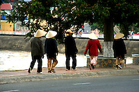 Vietnamese women in conical hats walking along the lake for their morning constitutional.  Dalat is Vietnam's favorite hill station and is very popular with Vietnamese travelers as well as foreign visitors.