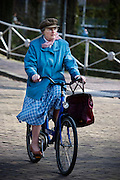 Een oudere vrouw fietst helemaal in het blauw door Utrecht