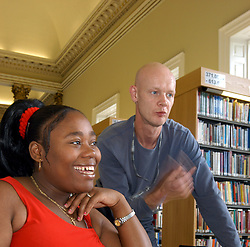 Student & course tutor working at computer in library; further education college; UK