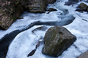 Latourell Creek, largely frozen over after a week of below-freezing temperatures, winds past boulders and other obsticles. The creek is located downstream from a major waterfall, one of many in Oregon's Columbia River Gorge.