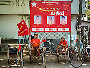 02 NOVEMBER 2015 - YANGON, MYANMAR: Pedicab drivers wearing NLD tee shirts wait for fares under a NLD poster in Yangon. National elections are scheduled for Sunday Nov. 8 in Myanmar. The two principal parties are the National League for Democracy (NLD), the party of democracy icon and Nobel Peace Prize winner Aung San Suu Kyi, and the ruling Union Solidarity and Development Party (USDP), led by incumbent President Thein Sein. There are more than 30 parties campaigning for national and local offices. PHOTO BY JACK KURTZ