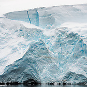 "A glacier of thick ice and snow gradually falls into the sea as it flows down the side of the mountains at the Lemaire Channel in Antarctica. The Lemaire Channel is sometimes referred to as ""Kodak Gap"" in a nod to its famously scenic views."