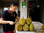11 DECEMBER 2018 - SINGAPORE:  A vender sets out his durian in the Haig Road Market and Food Centre in the Geylang neighborhood. The Geylang area of Singapore, between the Central Business District and Changi Airport, was originally coconut plantations and Malay villages. During Singapore's boom the coconut plantations and other farms were pushed out and now the area is a working class community of Malay, Indian and Chinese people. In the 2000s, developers started gentrifying Geylang and new housing estate developments were built.     PHOTO BY JACK KURTZ