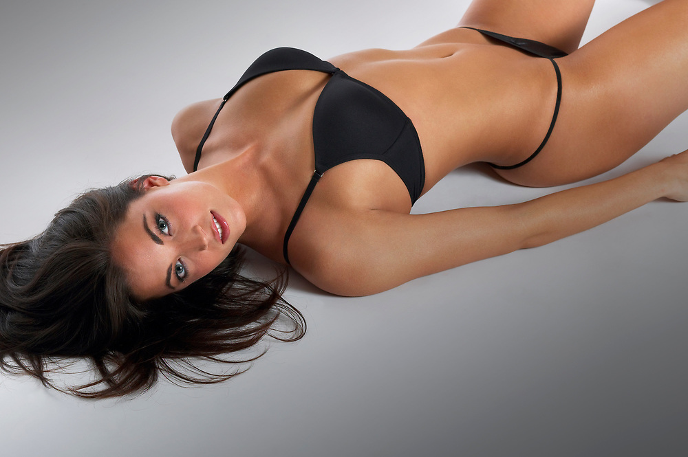 Woman in a black bikini reclining on white background with hair spread out