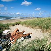 Nederland, Rotterdam 01 september 2008 20080901 Foto David Rozing .Tweede Maasvlakte, aanleg begonnen. Nudisten liggen te zonnen op naakstrand dat, tot hun spijt, door de aanleg van de tweede maasvlakte zal verdwijnen...Via een lange buis wordt zand uit de Eerste Maasvlakte naar het strand gepompt, om een eerste laag op te spuiten. Aan het project gingen 15 jaar vooraf van studies en besluitvorming. De kosten zijn begroot op 3 miljard euro. Daarin zitten ook de kosten voor de natuur- en recreatiegebieden die er komen als tegenwicht voor het nieuwe havengebied. De Tweede Maasvlakte kan straks schepen met de grootste diepgang ontvangen. De aanleg is begonnen hoewel er nog drie procedures van milieugroepen lopen. Rotterdam, 1 sept. Burgemeester Ivo Opstelten van Rotterdam gaf vanmorgen het startsein voor de aanleg van de Tweede Maasvlakte door de buis open te draaien waaruit uiteindelijk 290 miljoen kubieke meter zand moet stromen. Met het 2.000 hectare grote eiland op ongeveer drie kilometer van de kust wil de Rotterdamse haven zijn capaciteit tussen nu en 2013 met 20 procent uitbreiden. Met de aanleg is een investering van 2,9 miljard euro gemoeid..Aan de aanleg van Tweede Maasvlakte, een van de grootste infrastructurele projecten in Nederland, ging ruim vijftien jaar juridisch en politiek gesteggel vooraf. Met de uitbreiding moet de haven de concurrentie met andere containerhavens beter aankunnen. Vorig jaar was Rotterdam met een recordoverslag van ruim 406 miljoen ton goederen veruit de grootste haven in Europa. Wereldwijd is Rotterdam de nummer drie, dankzij de overslag van bijna 11 miljoen containers en de gestegen vraag naar stookolie....Foto David Rozing