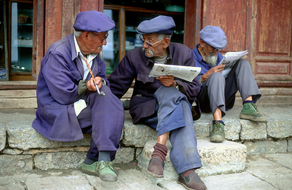Deep in conversation, two men from the Naxi ethnic minority group of Yunnan province wearing blue clothes sit, talk and listen intently.