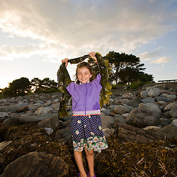 A young girl exploring a tidepool in Odiorne State Park in Rye, New Hampshire.