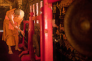 """Mar. 14, 2009 -- LUANG PRABANG, LAOS:  A monk uses a gong to call other monks to evening prayers at Wat Xieng Thong in Luang Prabang. The temple was built in 1560 and was a royal temple until the end of the Laotian monarchy in 1975. Luang Prabang is a UNESCO World Heritage Site and the spiritual capital of Laos. There are dozens of """"wats"""" or temples and thousands of monks in the city. It is still the center of Buddhist education in Laos.   Photo by Jack Kurtz"""