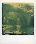 Old green and yellow toned Polaroid of an old arched stone bridge over a calm river with tree-lined banks, China, Asia