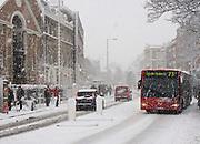 Bus and cars driving through heavey snow. Church Street, Stoke Newington, London.