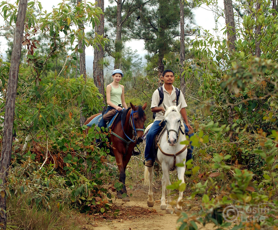 Grace Chandler, 12, of Houston, TX, is lead by a guide on a horseback ride around the Blancaneaux Lodge, one of Francis Ford Coppola's resorts, in the eastern part of Belize.<br />JUSTIN LANE FOR THE NEW YORK TIMES