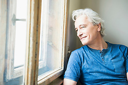 Mature man sitting in front of window, smiling