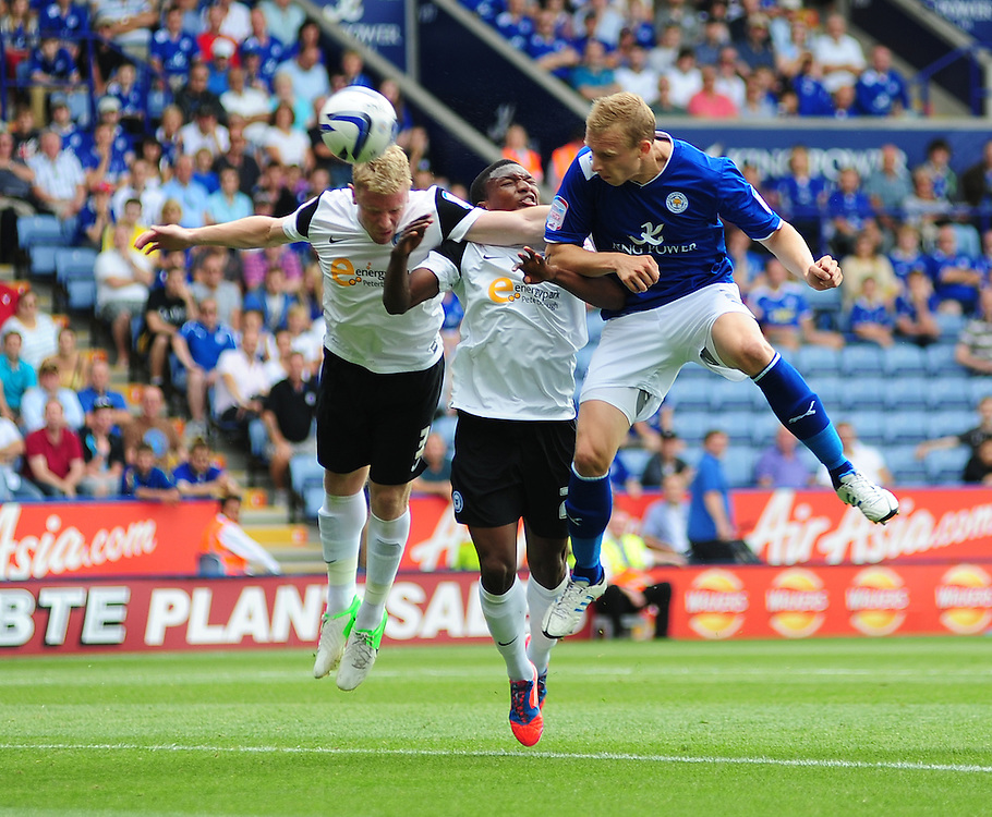Leicester City's Ritchie De Laet heads over the bar under pressure from Peterborough United's Craig Alcock, left, and Kgosi Ntlhe ..Football - npower Football League Championship - Leicester City v Peterborough United - Saturday 18th August 2012 - King Power Stadium - Leicester..