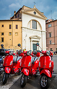Three red Vespas on Piazza di San Pantaleo in Rome, Italy