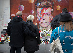 © Licensed to London News Pictures. 10/01/2017. London, UK. Fans gather at a mural and shrine to David Bowie in Brixton on the first anniversary of his death. David Bowie was born in Brixton, south London. Photo credit: Peter Macdiarmid/LNP