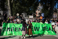 London, UK. 24th September, 2021. Young people stand behind a Green New Deal banner in Parliament Square during a Global Climate Strike to demand intersectional climate justice. The Global Climate Strike was organised to highlight the detrimental influences through colonialism, imperialism and exploitation of the Global North on MAPA (Most Affected Peoples and Areas), which have contributed to them now experiencing the worst impacts of the climate crisis, and to call on the Global North to pay reparations to MAPA.