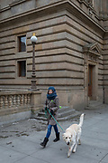 A stylish young woman walks her pet dog outside the National Theatre on Vodickova Street, on 19th March, 2018, in central Prague, the Czech Republic.