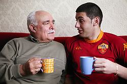 Grandfather and grandson at home drinking coffee,