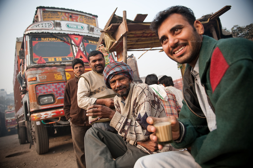 truck drivers having their first morning chai (Indian tea) at a truck depot on the outskirts of Delhi.