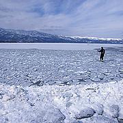 Japan, Japanese resident skiing across frozen Lake Kussharo. Japan.