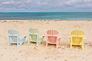 Pastel colored adirondack chairs on Love beach  in Nassau, Bahamas