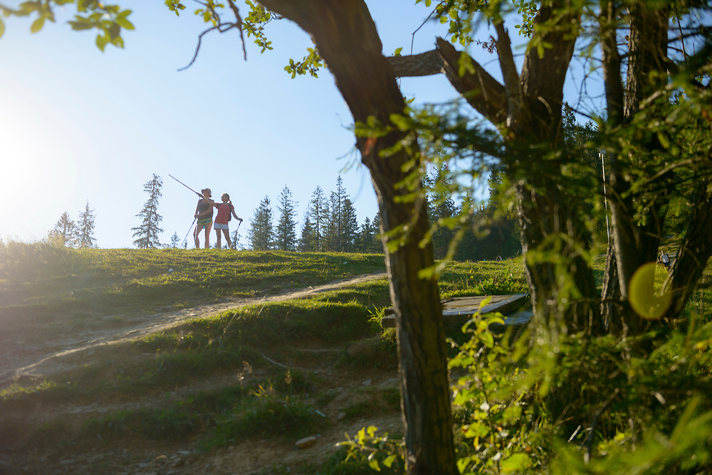Two women hike late on a summer afternoon on a hill above Zakopane, Poland