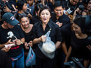 11 NOVEMBER 2016 - BANGKOK, THAILAND: YINGLUCK SHINAWATRA (holding sack of rice) sells a sack of rice to a woman at a rice distribution sale in the Bangkok suburbs. Yingluck Shinawatra, the former Thai Prime Minister deposed in a coup in 2014, has started selling rice directly to Thai consumers. She buys the rice from farmers at market prices and then sells it to urban consumers at the price she paid. She said she's doing it to help out farmers, who are trying to deal with depressed prices. Yingluck is facing prosecution on corruption related charges going back to a rice price support scheme her government used to try to help farmers in 2011 and 2012. Even after the coup, she is still personally popular and hundreds of people showed up to see her at the rice distribution point at a mall in Samut Prakan province, in suburban Bangkok.   PHOTO BY JACK KURTZ