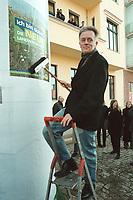 """06 MAR 2001, BERLIN/GERMANY:<br /> Fritz Kuhn, B90/Gruene Bundesvorsitzender, plakatiert das Plakat """"Ich bin dabei! Die neue Landwirtschaft"""" an eine Litfastsaeule vor der Bundesgeschäftsstelle Buendnis 90/Die Gruenen <br /> IMAGE: 20010306-01/01-34"""