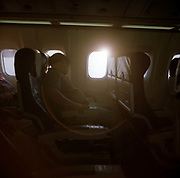 As bright sunlight shines through the window of an airliner, a sleeping male passenger reclines in his seat on a generic transatlantic flight. Sitting in the window seat of this transatlantic flight, the man has a large tummy protruding over his seat belt as he slumbers with a hand resting on the seat arm. The sun is over the port (left) wing as it continues to fly back towards Europe from the USA.