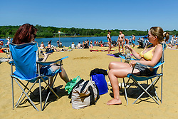 © Licensed to London News Pictures. 25/05/2020. LONDON, UK.  Women sit in the sun taking advantage of the easing of certain coronavirus pandemic lockdown restrictions to enjoy the sunshine and warm weather on Bank Holiday Monday at the beach at Ruislip Lido in north west London. The UK government continues to remind the public adhere to social distancing when outdoors and to wear a face covering where social distancing is not possible.  The forecast is for temperatures to rise to 25C, with similar conditions for the next few days. [*** PERMISSION OBTAINED ***]  Photo credit: Stephen Chung/LNP