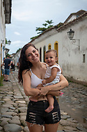 Isabeli, holding her nine-month old daughter Serenah, in the colonial town of Paraty, Brazil. (March 15, 2019)