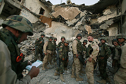 The description of an dead Iraqi UN worker is told to U.S. soldiers from the 203rd Engineers within the 1st AD as the prepare to comb the site of the explosion  at the Canal Hotel for bodies Aug. 21, 2003 in Baghdad, Iraq. The previous day a cement truck packed with explosives detonated outside the offices of the UN headquarters in Baghdad, Iraq, killing 20 people and devastating the facility in an unprecedented suicide attack against the world body. At least 100 people were wounded.