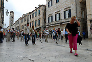 Low-angle view of people walking through Stradun (or Placa), the main street of Dubrovnik old town, Croatia