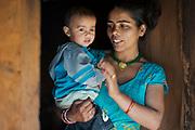 Srijana Phuyal and her 18 month-old daughter, Riya in the doorway of their home, Kakani, Nuwakot District, Nepal