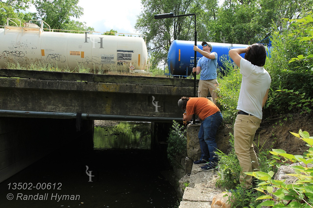 Train passes as Hyfi CEO Brandon Wong (foreground) and field techs Nik Krantz and Matt Craddock (l,r) install wireless water-level sensor along stormwater creek for the Northeast Ohio Regional Sewer District in Metro Cleveland, Ohio.