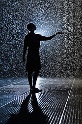 © licensed to London News Pictures. London, UK 03/10/2012. A Barbican Centre staff posing in Random International's Rain Room installation, which featuring 100 square metres of pelting water falling from around 4 metre high at The Curve Gallery in Barbican Centre, London. When visitors walk through the rain stops around them. Photo credit: Tolga Akmen/LNP