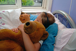 Upset girl in bed with her teddy bears