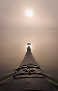 The sun rises over the bow of a kayak through a fall morning fog on the May River.