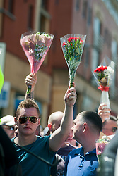 An EDL organised event to lay flowers at Sheffields War Memorial in Barkers Pool in Memory of Lee Rigby on Saturday afternoon was stopped by supporters of Sheffield Unite Against Fascism and One Sheffield Many Cultures. EDL hold flowers in the air while kept back from the supporters of Sheffield Unite Against Fascism and One Sheffield Many Cultures and Sheffield War memorial by a police Cordon<br /> <br /> 1 June 2013<br /> Image © Paul David Drabble<br /> www.pauldaviddrabble.co.uk