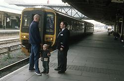 Guard talking to passengers on platform at railway station,