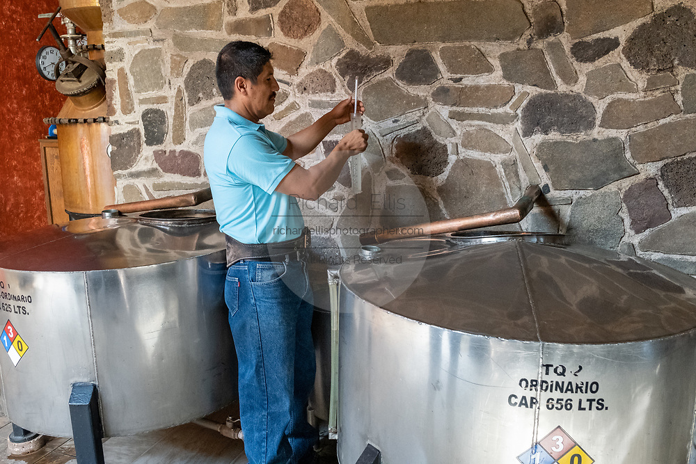 A worker checks the gravity of fresh tequila from the still before it is put in barrels for aging at the Casa Siete Leguas, El Centenario distillery in Atotonilco de Alto, Jalisco, Mexico. The Seven Leagues tequila distillery is one of the oldest family owned distilleries and produces handcrafted tequila using traditional methods.