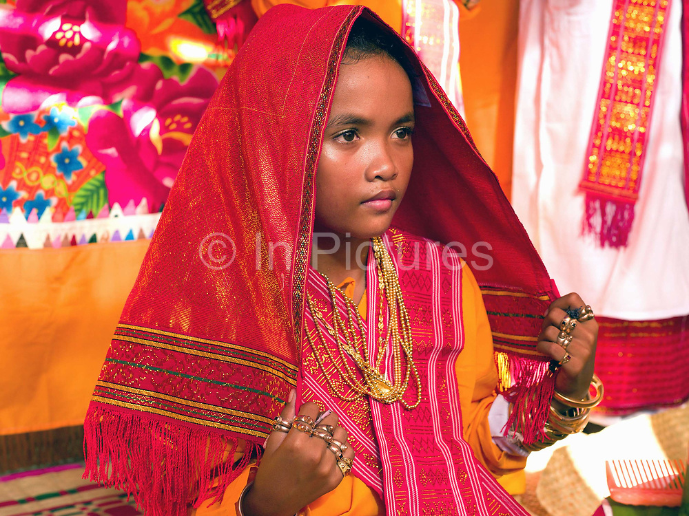 A Muslim Cham girl wearing a white dress, a handwoven red cloth and bronze and copper jewellery at her Karoh (maturity) ceremony in Van Lam, Ninh Thuan province, Central Vietnam. Cham girls usually in groups of around 5, undergo a Karoh (maturity) ceremony, one of the most important ritual events of their lives and if it has not taken place, the girl cannot marry. The Cham, a Muslim community of around 39,000 people living along the coast of Central Vietnam are one of the 54 ethnic groups recognised by the Vietnamese government.