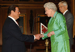 File photo dated 03/05/06 of Queen Elizabeth II with Help The Aged Living Legend award winner, Sir Roger Moore, and 'compere', Michael Parkinson, right, at a ceremony at Windsor Castle. Sir Roger has died in Switzerland after a short battle with cancer, his family has announced.