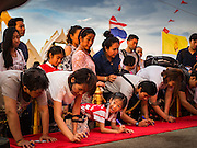 20 NOVEMBER 2015 - BANGKOK, THAILAND:  People write prayers on a red cloth that will be wrapped around the chedi at the top of Wat Saket during the annual temple fair. Wat Saket is on a man-made hill in the historic section of Bangkok. The temple has golden spire that is 260 feet high which was the highest point in Bangkok for more than 100 years. The temple construction began in the 1800s in the reign of King Rama III and was completed in the reign of King Rama IV. The annual temple fair is held on the 12th lunar month, for nine days around the November full moon. During the fair a red cloth (reminiscent of a monk's robe) is placed around the Golden Mount while the temple grounds hosts Thai traditional theatre, food stalls and traditional shows.    PHOTO BY JACK KURTZ