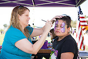 Jennifer Cullenbine paints Marissa Buzenes' face, 11, at the Family Giving Tree booth during Relay For Life at the Milpitas Sports Center on June 23, 2012.  Photo by Stan Olszewski/SOSKIphoto.
