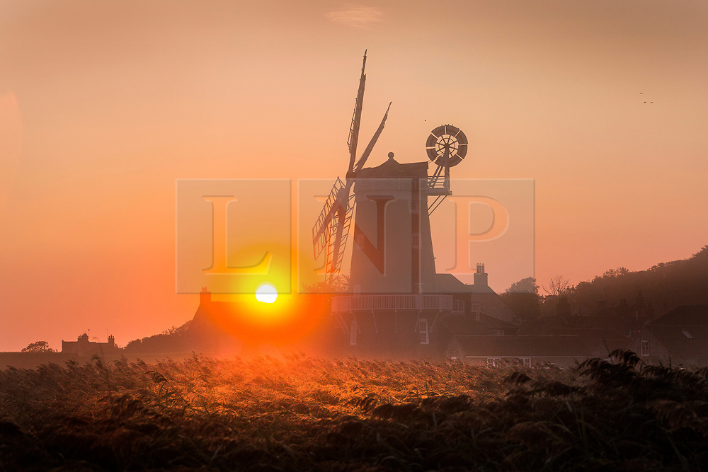 © Licensed to London News Pictures. 03/09/2018. Cley Next The Sea UK. The sun rises this morning behind the 19th century Cley Windmill in Cley next the Sea on the Norfolk coast. Photo credit: Andrew McCaren/LNP