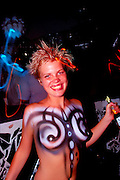 Working topless with just body paint at a South Beach club named Groove Jet is waitress Anne Wiklund in May 1999, during South Beach's peak. She signed a photo release permitting publication of this photo for editorial and documentary uses.